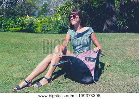 Woman With A Big Luxury Snakeskin Fashion Python Bag In The Park Of Nusa Dua, Bali Island, Indonesia