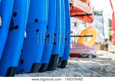 Set Of Blue Surf Boards In A Stack By Ocean. Bali, Indonesia. Surf Boards On Sandy Nusa Dua Beach.