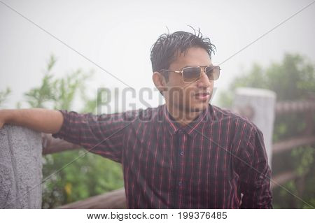 a portrait of a young asian man with sunglass and t shit with rain shower .