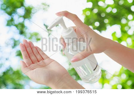 hand pouring alcohol-based sanitizer himself green bokeh background