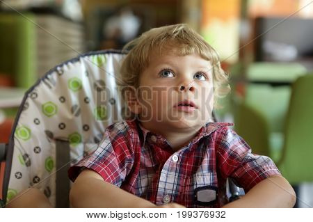 Portrait of a kid in a highchair