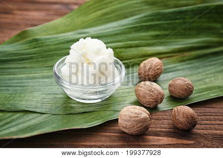 Shea butter in bowl and nuts on wooden table