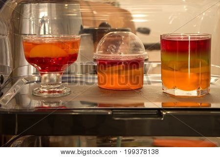 Soft drinks are shown in display case natural fruit juices with ice and lemon. Refreshing fruit sangria (punch) drink with ice.