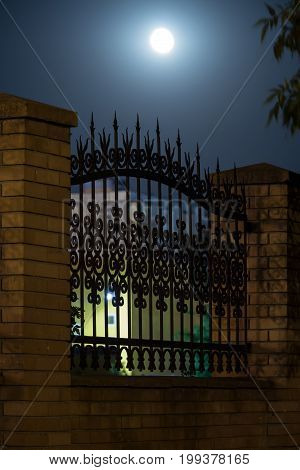 Wrought iron bars of a fence in the form of a spear in the night sky forging and stone wrought-iron ornaments.