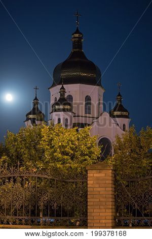 Town church with a cross against the backdrop of night sky at full moon