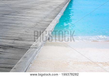 Wooden pontoon on beach in summer day