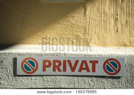 private no parking sign in german language in front of wall