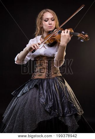 Blond woman playing the fiddle on black background