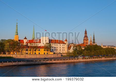 Old Riga castle at sunset. Waterfront of old town over Daugava River.