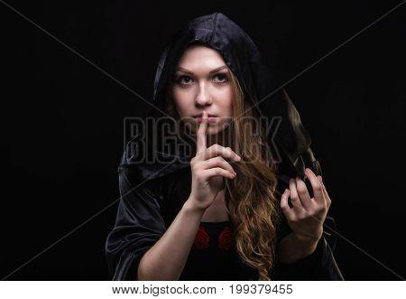 Blond girl in hood showing quiet gesture on black background