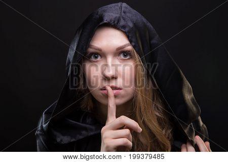 Blond girl showing quiet gesture on black background