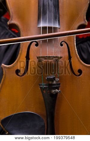 Photo of violin and fiddlestick, closeup on black background