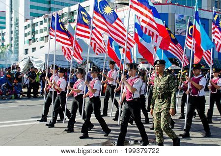 Kota Kinabalu Malaysia - August 31 2016: Participants waving a Malaysian flags during Malaysia's 59th Independence day parade held in Kota Kinabalu City Square.