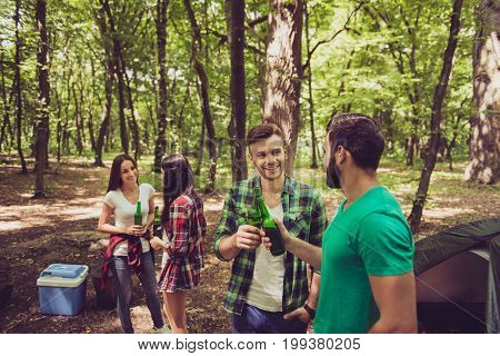 Four Cheerful Tourists Friends Are Chilling In The Summer Woods, Having Beer, Good Sunny Day, Campsi