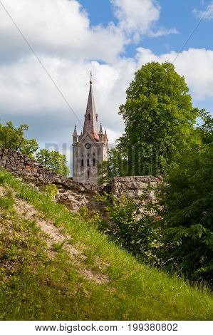 Cathedral and beautiful ruins of ancient Livonian castle in old town of Cesis, Latvia. Greenery and summer daytime.