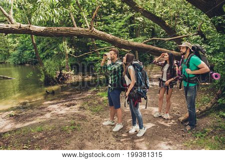 Exploring, Researches And Expedition Concept. Four Tourists Are Hiking Near The River In A Wild Spri