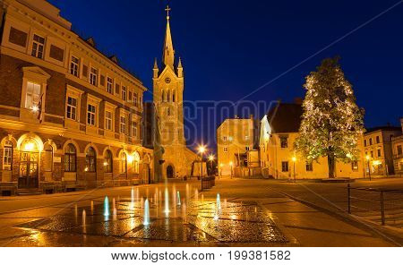 Medieval church of Saint John and night old town view of Cesis, Latvia.