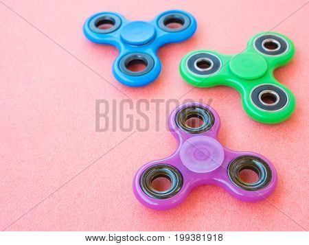 Popular colourful fidget spinner toy on a colored background.