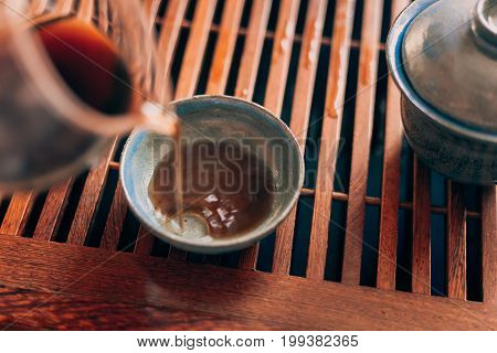 Brewed tea is poured into the bowl on tea-board, gaiwan,  Chinese tea ceremony, selective focus, toned