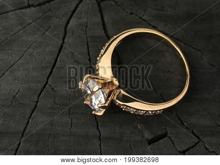 Jewelry ring with diamond on black wood background