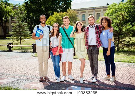 Study together is fun teamworkteambuilding concept. Six happy students are standing near university building and holding book wearing casual smart smiling and embracing on a sunny spring day