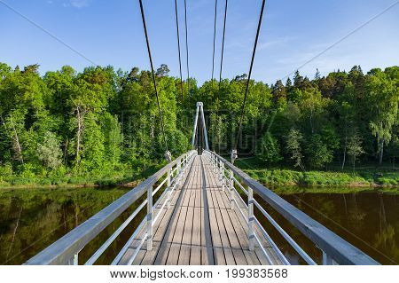 Cable-stayed wooden path bridge over Gauja river with forest at the background