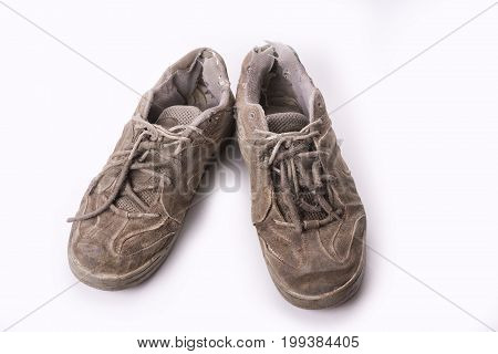 Old wear out tennis shoes isolated on white background