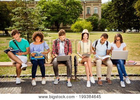 It`s more easy together! Six cheerful classmates are sitting on a bench in spring sunny park near campus and study preparing for exams tests with books notepads laptops tablets