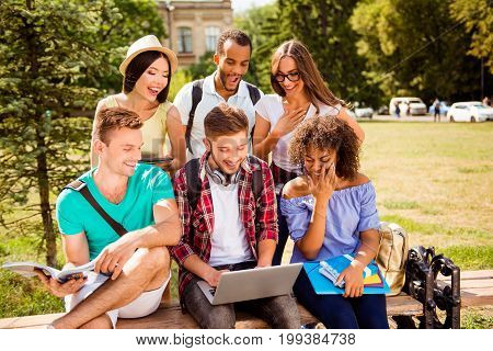 It`s so fun and easier together! Six happy multi ethnic students are learning outdoors in a sunny park with book note pads and devices dressed comfortable laughing