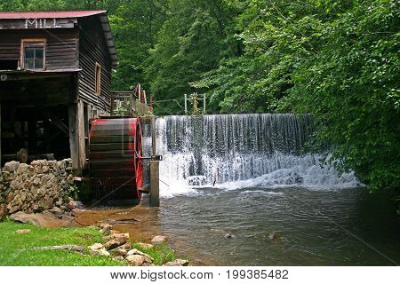 water pours over a dam next to a gristmill