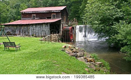water pours over a dam next to a gristmill, bench in foreground