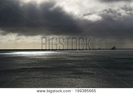 Seascape dark clouds and rain approaching, ships sheltering