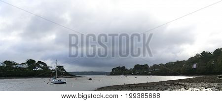 Cornish river estuary with cloudy skies on bright day