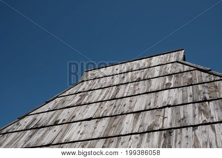Old shake roof with weathered wooden planks and deep blue sky above