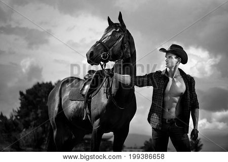 Macho man handsome cowboy with amazing muscles and abs and horse are on the background of sky and water. Western style poster
