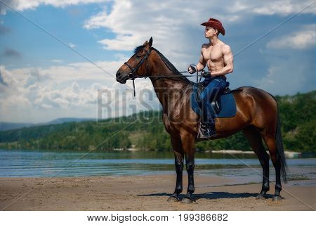 Macho Man Handsome Cowboy Riding On A Horse On The Background Of Sky And Water.