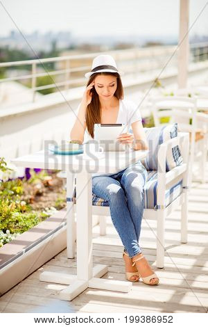 Relaxed And Tasty Pause! Young Pretty Lady Tourist In Casual Outfit And Hat Is Browsing News At Her