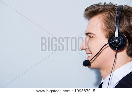 Side profile portrait of a handsome guy call centre operator in a headset. He is isolated on a pure light background wearing formal wear smiling