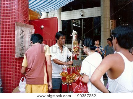 SINGAPORE / CIRCA 1990: A blind peddler offers items for sale outside the Kwan Im Thong Hood Cho Temple.