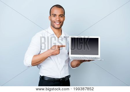 Copy Space Concept. Young Handsome Mulatto Banker On The Pure Light Blue Background Is Pointing On A