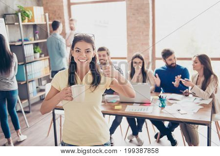 Cheerful Young Mulatto Girl Is Enjoying The Coffeebreak With Partners, Showing Thumbup Sign, Smiling