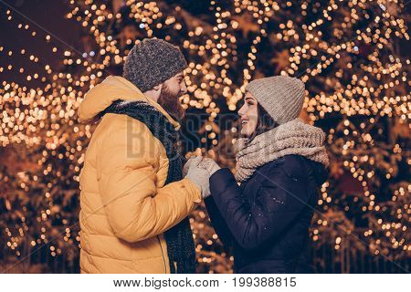 Side Profile View Of Young Red Bearded Man Making Proposal Of Marriage On Christmas Eve Outdoors To