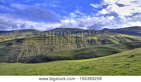 View of a green mountain range, part of the Ecuadorian Andes, with a beautiful sunny and cloudy sky. Cayambe, Ecuador.