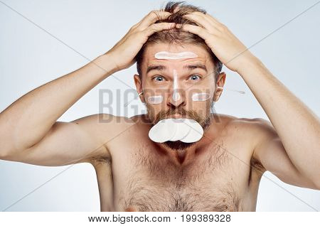 Man with a beard on a light background, cosmetic cream, ear wand, cotton wool, portrait, emotion.