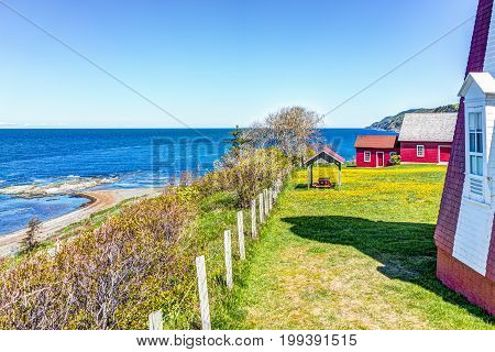 Red Painted Shed With Yellow Dandelion Flowers And View Of Saint Lawrence River In La Martre In The