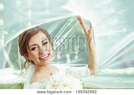 Closeup shot of elegant, brunette bride posing under veil closeup. Bride portrait wedding makeup fashion bride. Beautiful bride in veil. Toned