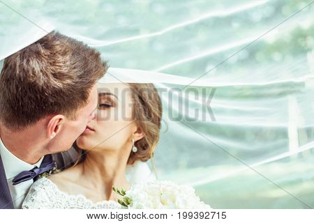 Portrait of young bride and groom together under the wedding veil. Loving wedding couple outdoor. Toned