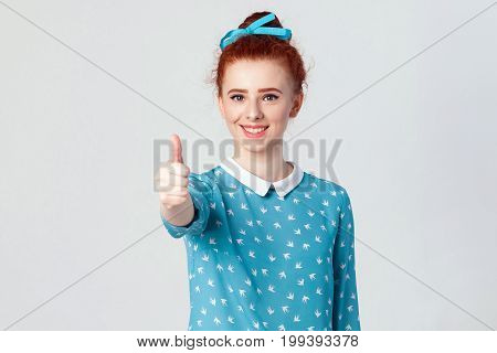 Young happy cheerful redhead girl showing thumb up and toothy smile. Isolated studio shot on gray background