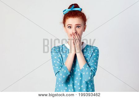 Portrait of serious young ginger. Caucasian girl covering mouth with both hands keeping a secret. Beautiful redhead female in blue dress doesn't want to spread rumors or some confidential information. Isolated studio shot on gray background.