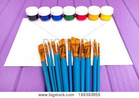 Top view of close cans of colored paint with brushes and sheet of paper on the purple wooden background